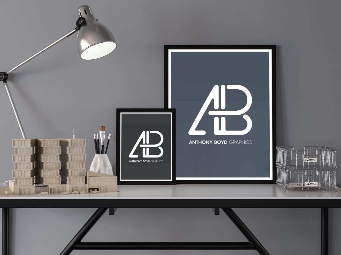 Image of 2 framed photos on a desk with lamp